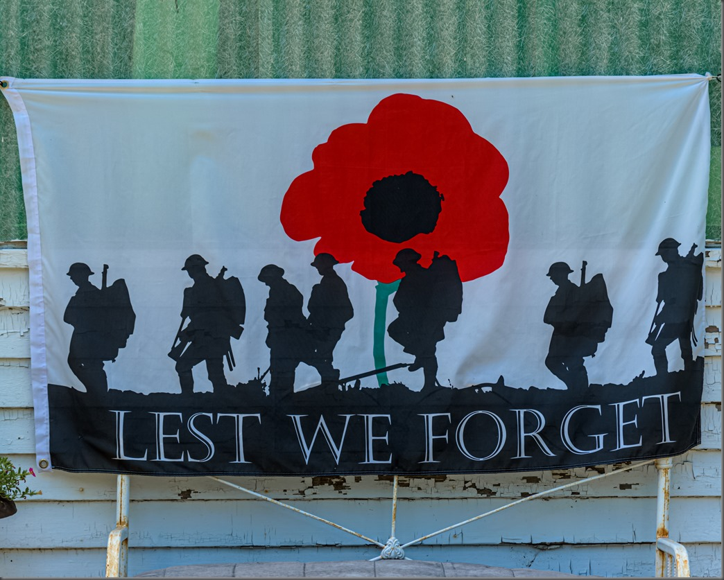 A red poppy on a banner with soldiers in combat gear walking across the battlefield